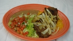 Carne Asada - A thin slice of steak grilled and served with beans, rice, tortillas and guacamole salad.